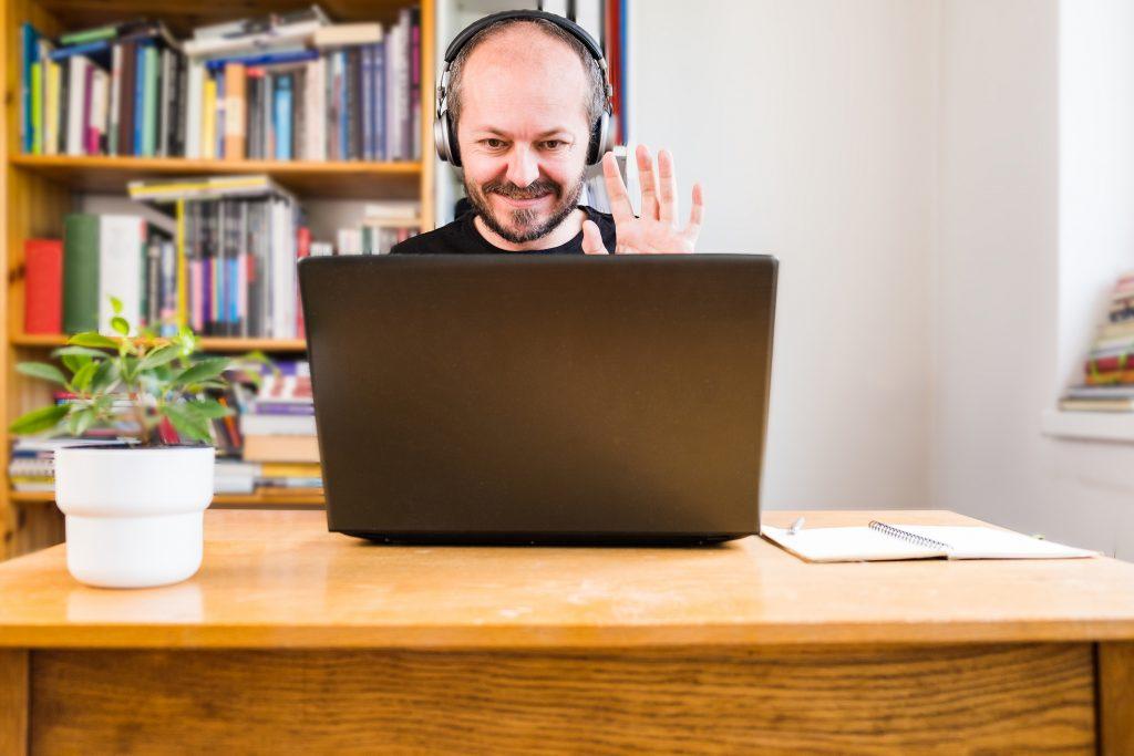 Man waving to computer